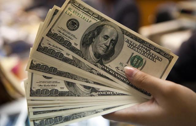 Persona con billetes de dólares